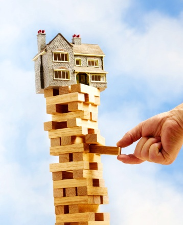 Toy house balancing on tower of wooden bricks, mans hand removing one block